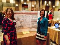 APBS 2014 Student Poster Award winners Sarah Gaines and Candace Gann standing in front of their poster