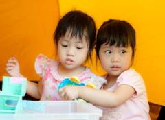 Two toddler girls in front of a plastic bin full of toys sharing a toy truck