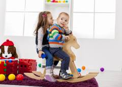 Two toddlers, a boy and girl, sitting together on a rocking-horse.