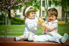 Two toddlers sitting outside on a sunny day fighting over a juice cup.  One of the toddlers is crying.
